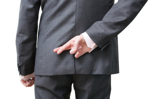 Man in suit with fingers crossed behind his back